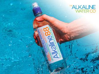 Hand holding Alkaline 88 water bottle