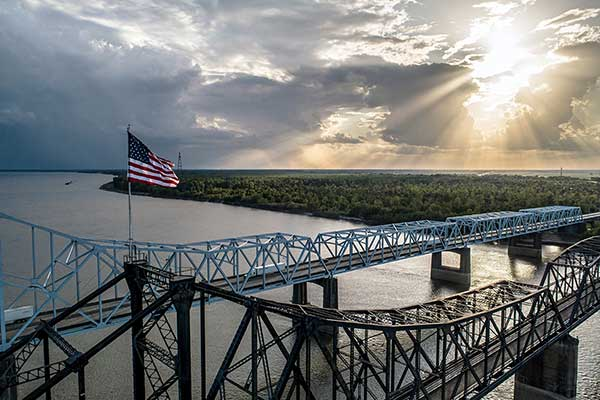 American flag flying on a bridge at sunrise