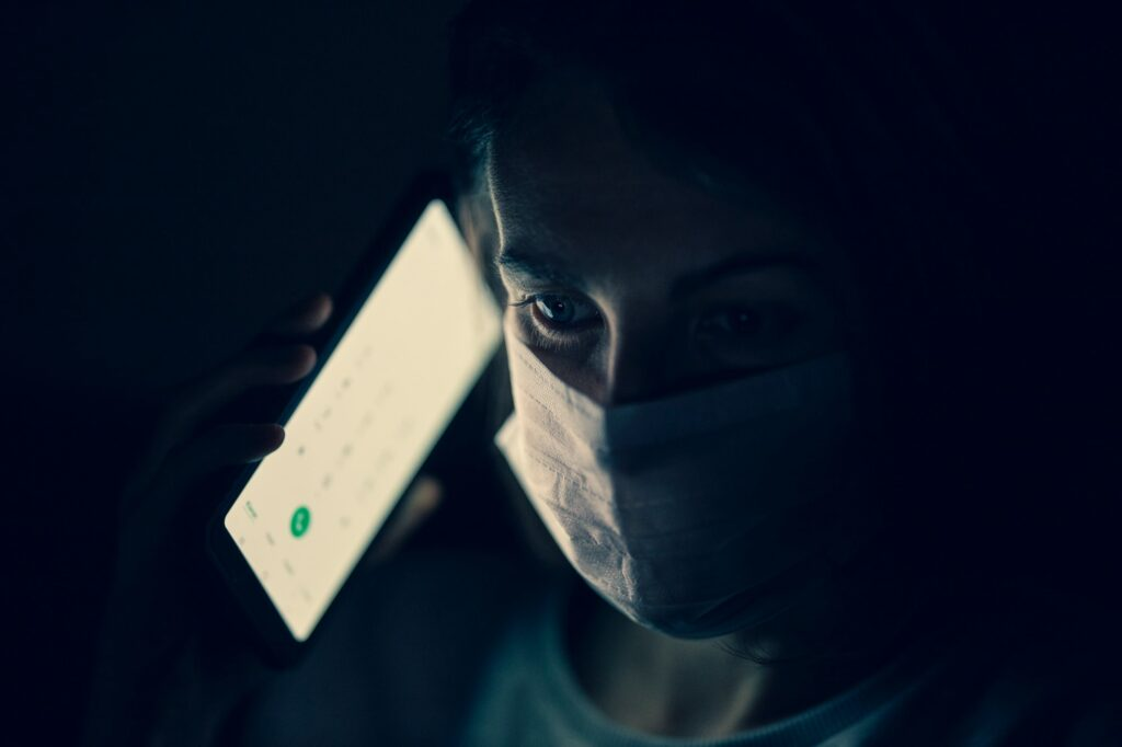 Person wearing a face mask on a call on their mobile phone
