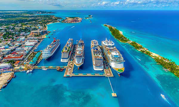 5 different cruise ships docked in harbour in the Bahamas.