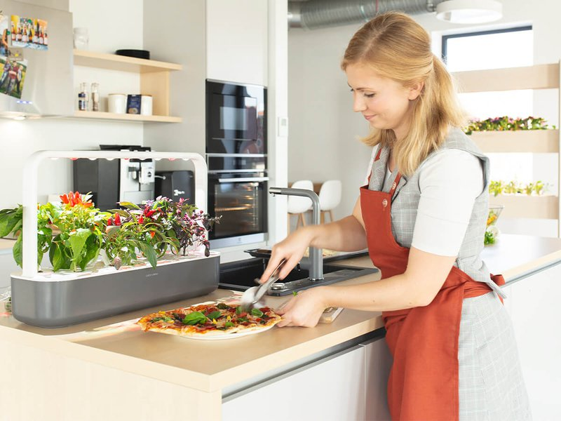 woman wearing apron cutting a pizza on kitchen worktop beside Click & Grow Smartpots