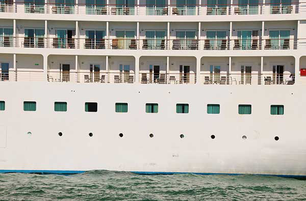 Close-up view of a huge cruise ship in the harbor of Venice, district Santa Croce. Balconies and chairs, no passengers are on board. Italy, Europe.